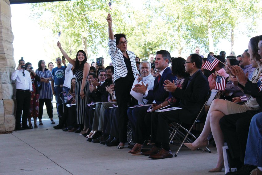 Women from Morocco stand and wave American flags as their country is named in recognition during a naturalization ceremony Sept. 25 at Centennial Center Park.
