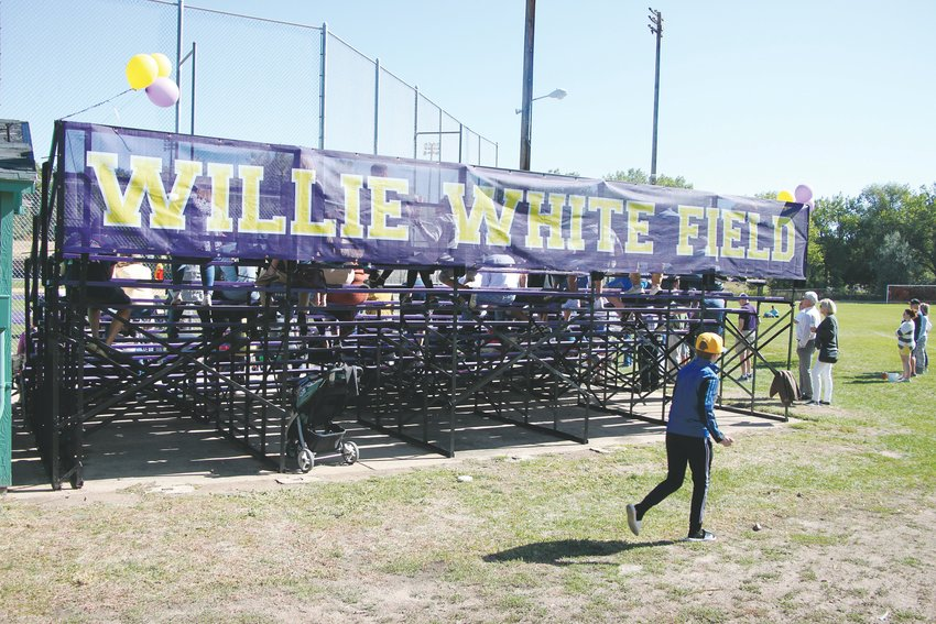 A boy runs past the bleachers at the Littleton High School baseball field, newly renamed after former coach Willie White.