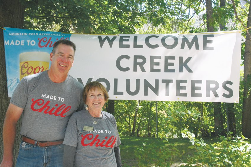 Craig Poupore, vice president of Golden valley operations at the Coors Brewery, and Golden Mayor Marjorie Sloan have their picture taken together under the welcome sign that greeted the nearly 150 volunteers who participated in the annual MolsonCoors Clear Creek cleanup on Sept. 26.