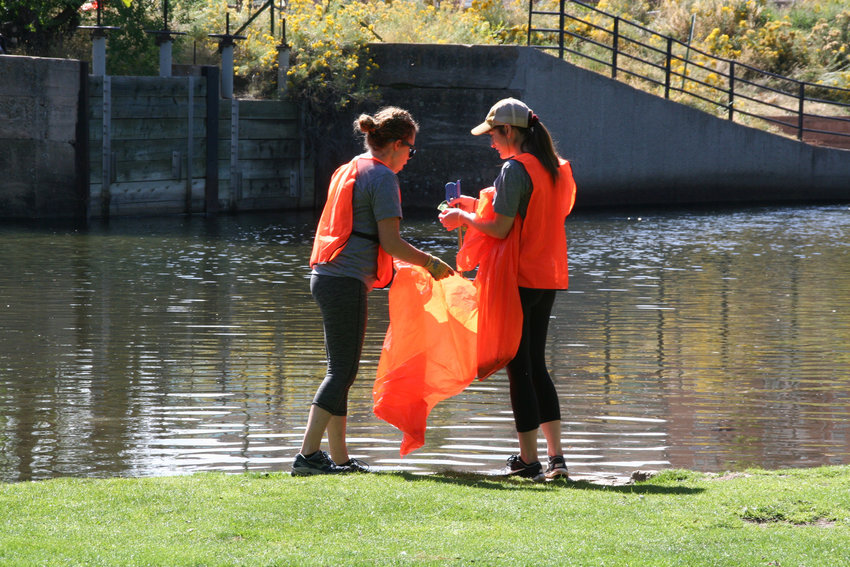Emily Kosel, left, and Julian Cuomo, who both work in the Coors Brewery's customer supply chain, work together to collect garbage along Clear Creek on Sept. 26 for MolsonCoors' annual Clear Creek cleanup.