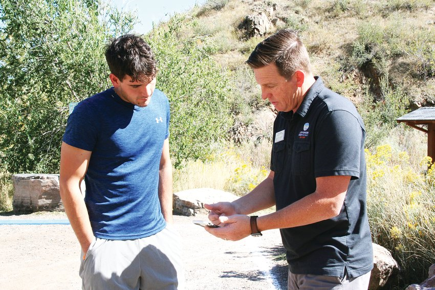 On the right, Matt Robbins, community connections manager for Jeffco Open Space, shows Golden resident Hunter Klein the new Lot Spot app on his mobile device at Mount Galbraith park.