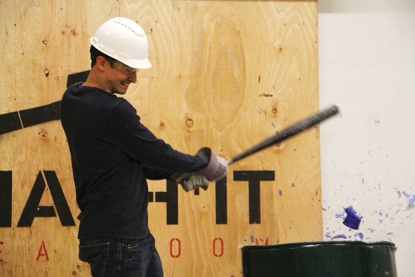 Dustin Gagne, an owner and founder of Smash It Breakroom, shatters a vase with a baseball bat Sept. 24 at his business in west-central Denver.