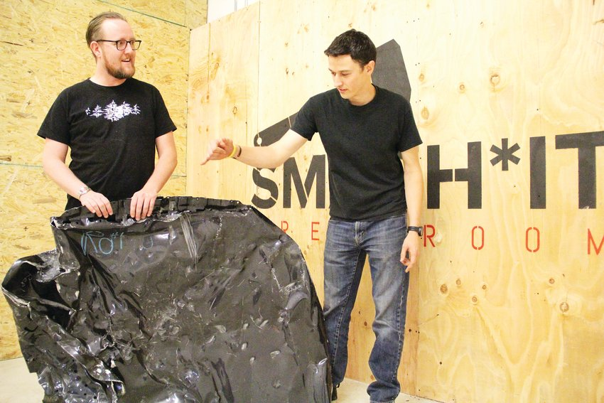 Drew Neilson holds a busted-up car hood while Dustin Gagne points to damage Sept. 24 at their business, Smash It Breakroom. Called a rage room or smash room, it bills itself as fun, safe stress relief.