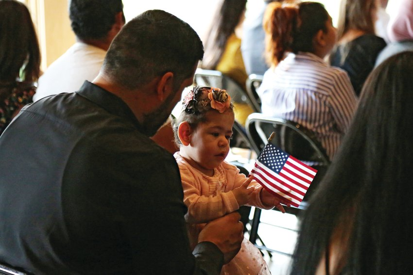 Emily Sophia Ochoa plays with an American flag while her mom becomes an U.S. citizen at a Sept. 6 naturalization ceremony.