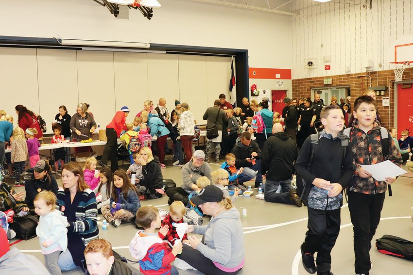 After walking to school, students and their families enjoy breakfast in the school gym as they wait for class to begin.