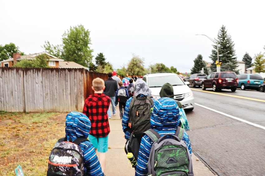 Side-by-side, Warder students walk to school in the rainy morning weather.