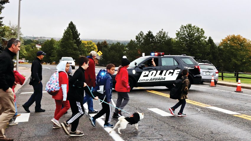The walk-to-school crowd crosses the street and waves to a member of the Arvada Police Department, which comes out every year to ensure kids are safe during the event.