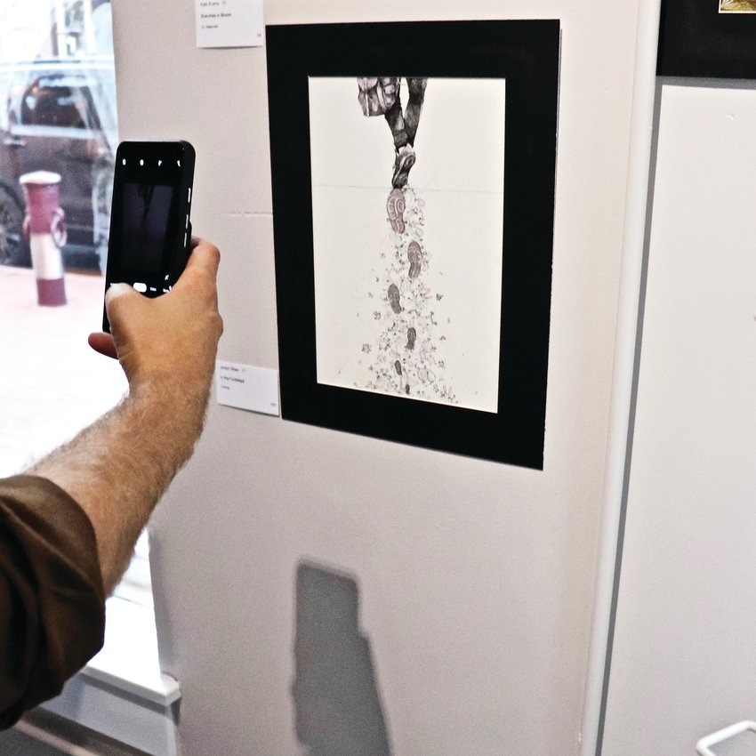 "Parson takes a shot of ""In the Footsteps"" by student Jordyn Shen, which was hung in Vouna, a clothing and accessories store."