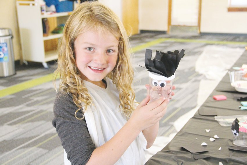 Paisley Monson, 6, holds up a craft she worked on at Smoky Hill Library's Oct. 3 Fun with Franken-slime event.