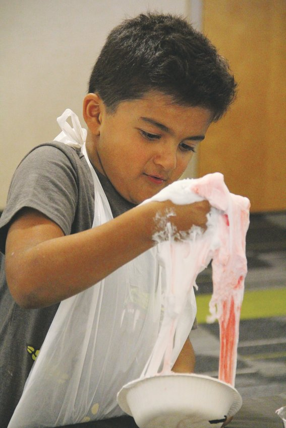 Bilaal Dawood, 7, grabs a fistful of slime Oct. 3 at Smoky Hill Library, where kids made slime and used it to create small creatures in the Halloween spirit.