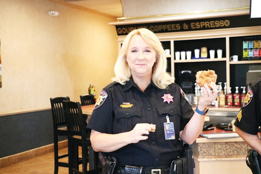Cocha Heyden, a spokesperson for the Douglas County Sheriff's Office, enjoys a donut during the community event intended to help residents get to know law enforcement.