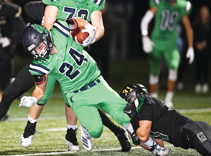 ThunderRidge's Lucas Fish (24) stretches for a few more inches as Mountain Vista's Joe Beck (31) holds on. The Grizzlies overcame a slow start to end on top after 2OT's 24-17 Thursday night at Shea Stadium.