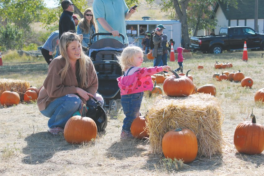 Ella Jansma kicks the tire on a fine looking pumpkin Oct. 5 at the Schweiger Ranch Fall Festival as her mother, Anna, watches.