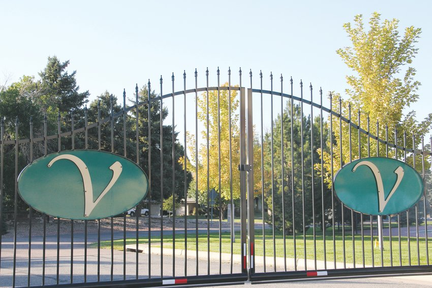 Gates at the south entrance to the Valley Club Acres neighborhood, where some homes sit just off a golf course. East of the gates, a Centennial shopping center is located along East Arapahoe Road.