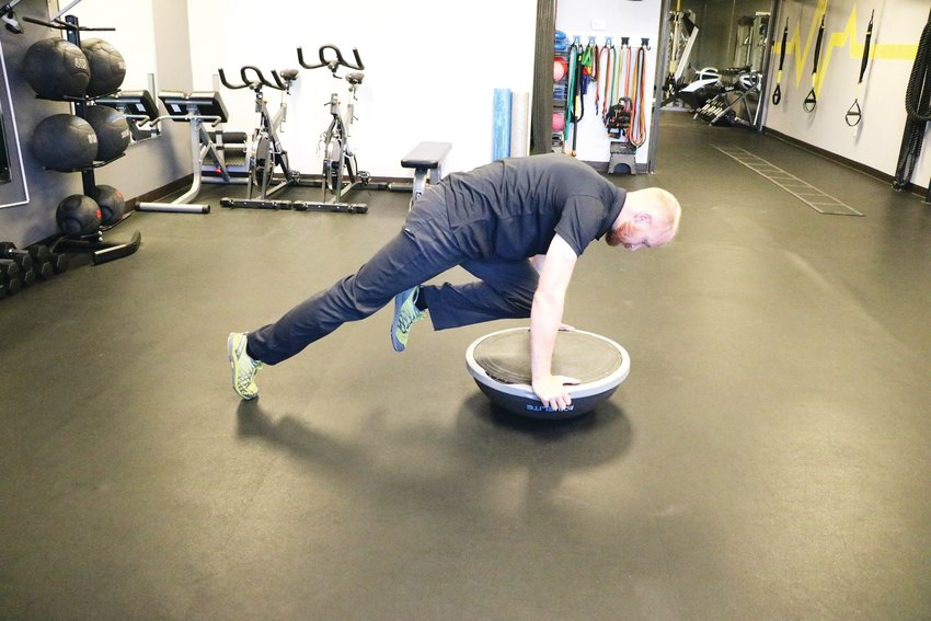"Davis shows how to do ""mountain climbers"" using a Bosu ball. Broc Thompson, coach of the Jeffco ski team, recommends using this tool with multiple exercises to increase stability, he said."