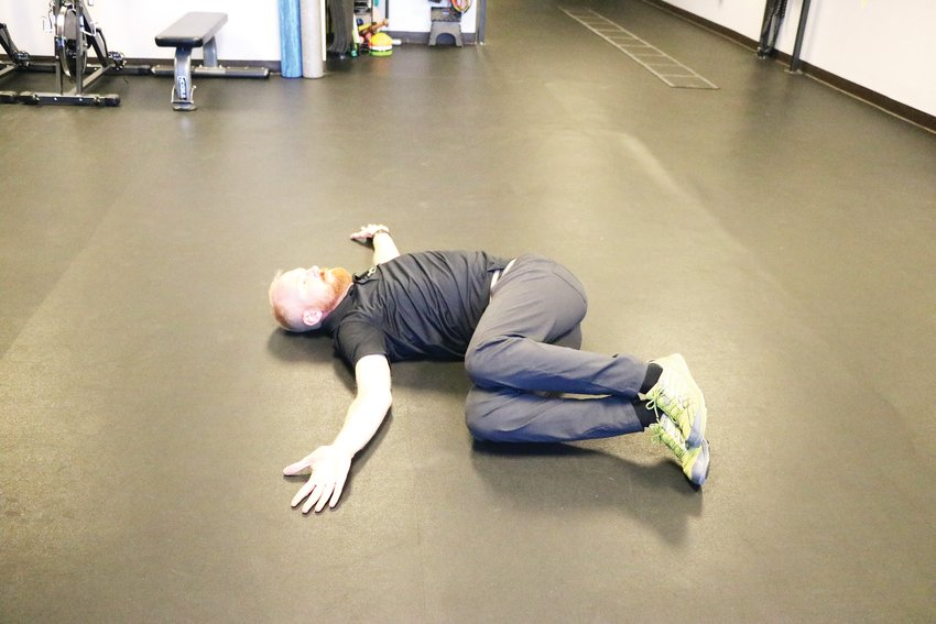 Davis demonstrates one side of a mobility exercise he recommends for skiing. One should start with knees bent in the air and then alternate sides, he said.