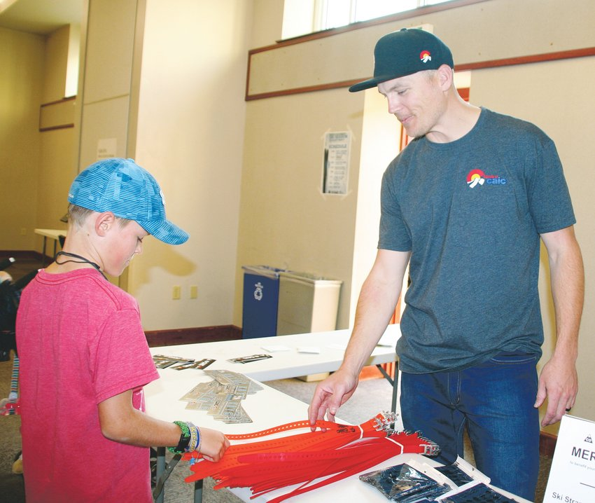Brian Rodine, right, the marketing and events manager for the Friends of the Colorado Avalanche Information Center (CAIC), explains the many uses of a ski strap to Miles Hoopes, 9, of Golden .