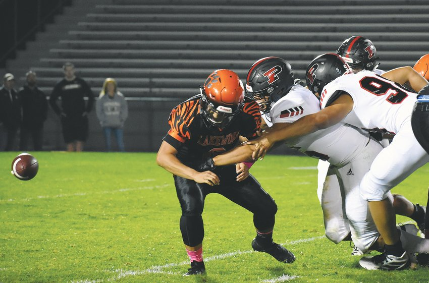 Pomona senior Sanjay Strickland, middle, knocks the ball out of the hands of Lakewood quarterback Jason Duong in the second quarter. Pomona junior AJ Zamora picked up the fumble to score the lone touchdown of the first half Thursday, Oct. 3, at Jeffco Stadium.