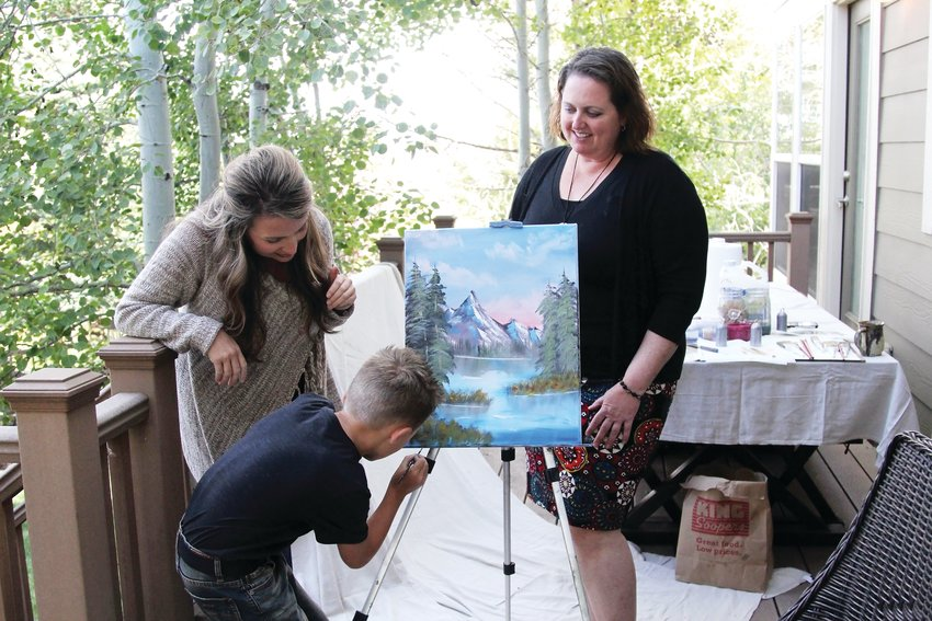 Jessica Clinger, left, watches her 8-year-old son, Titus, sign his initials on a painting inspired by Bob Ross. Titus' art teacher, Kimberly D'Arthenay, right, said Titus' painting proficiency is advanced for his age.