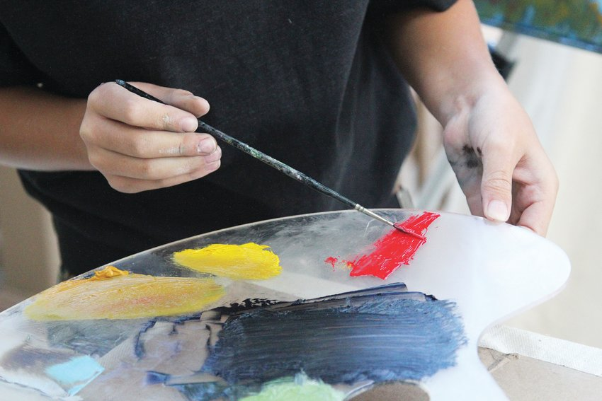 Titus Clinger works with oil paints, a medium his art teacher Kimberly D'Arthenay said is advanced for an 8-year-old student.