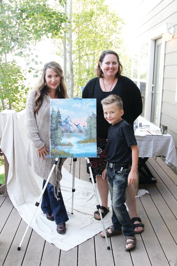 Titus Clinger, 8, stands next to his painting along with his art teacher, Kimberly D'Arthenay (right) and his mother, Jessica Clinger (left).