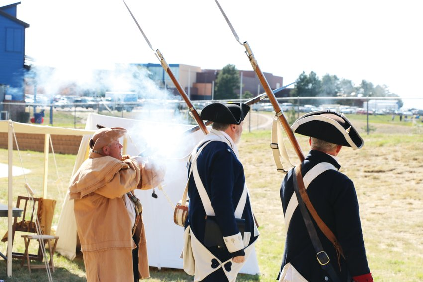 Sons of the American Revolution conduct a firing salute during a colonial reenactment at Cresthill Middle School Oct. 9.