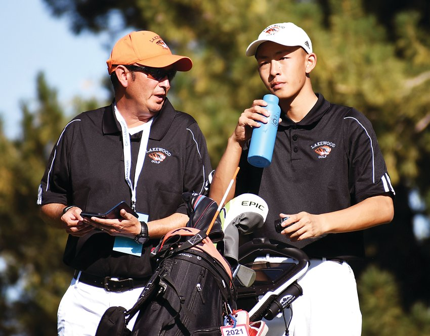 Lakewood boys golf coach Alan Gonzales talks with Lakewood junior Ryan Liao on the tee box during the final round of the Class 5A boys golf state tournament Oct. 8 at Pinehurst Country Club in Denver.