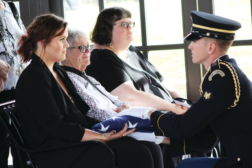 Alexis Rae Redman is presented with an American flag in honor of her late father, Christian Redman, of the 11th Armored Cavalry Regiment, Oct. 17 at Fort Logan National Cemetery.
