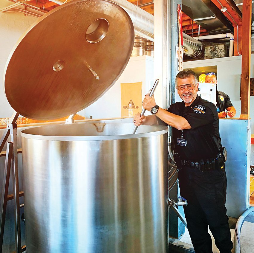 Elizabeth Chief of Police Stephen Hasler stirs the pot while helping create a specialty brew at The Elizabeth Brewing Company.