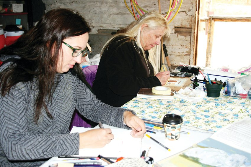 In the front, Melody Huisjen of Golden sketches the door inside the Golden History Park's Reynolds Cabin while Janine Sturdavant of Golden paints the root cellar at the history park during Foothills Art Center's Open Studio paint out on Oct. 18.