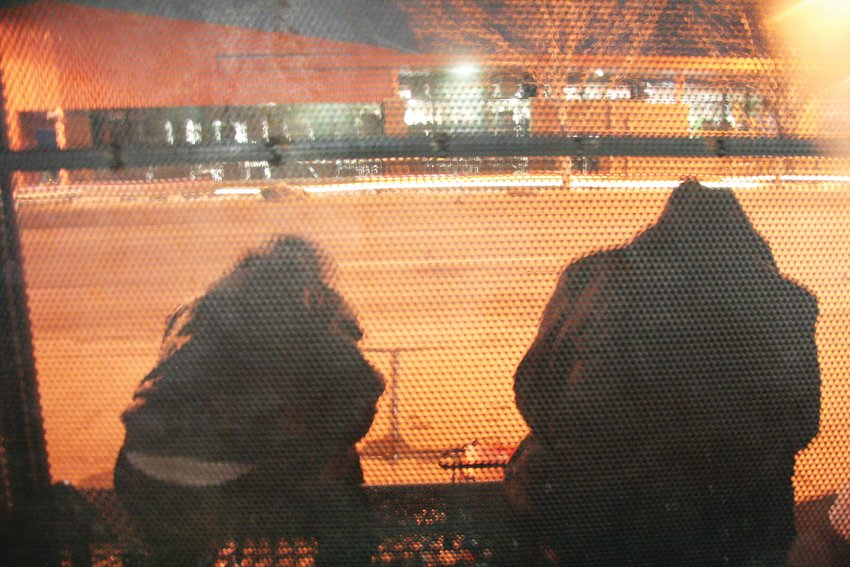 A homeless man and woman sit on a bench along Colfax Avenue in Lakewood during a January evening.