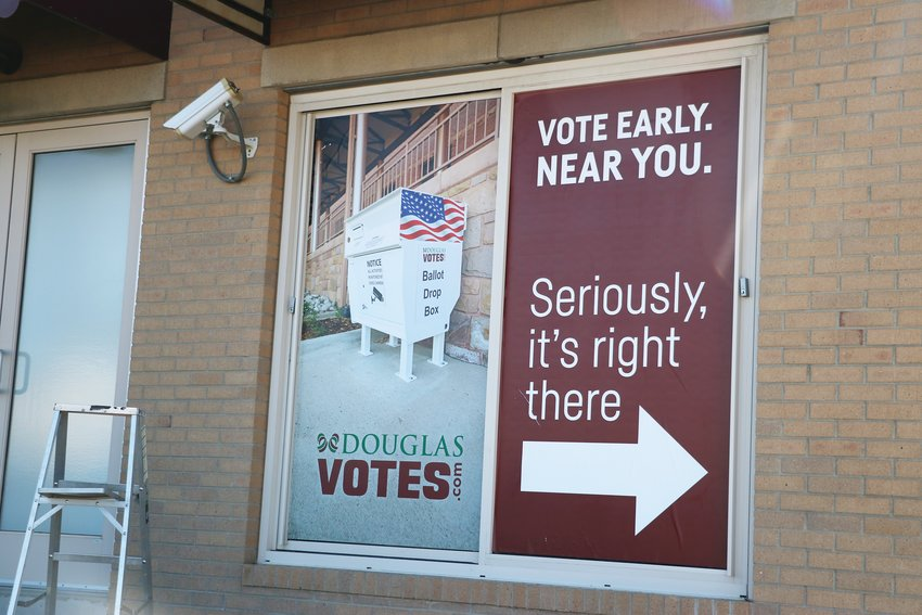 A new sign by the Douglas County Office Building offices on Third Street encourages voters to submit their ballots at a nearby drop box.