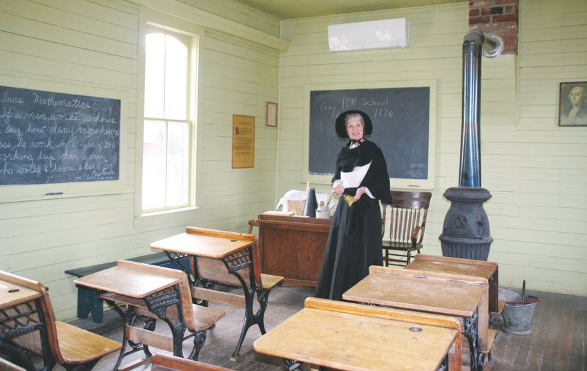 Carolyn Grenier, a volunteer with the Golden History Museum & Park, stands inside the 1876 Guy Hill schoolhouse located at the history park, which is near 11th and Arapahoe streets in Golden.