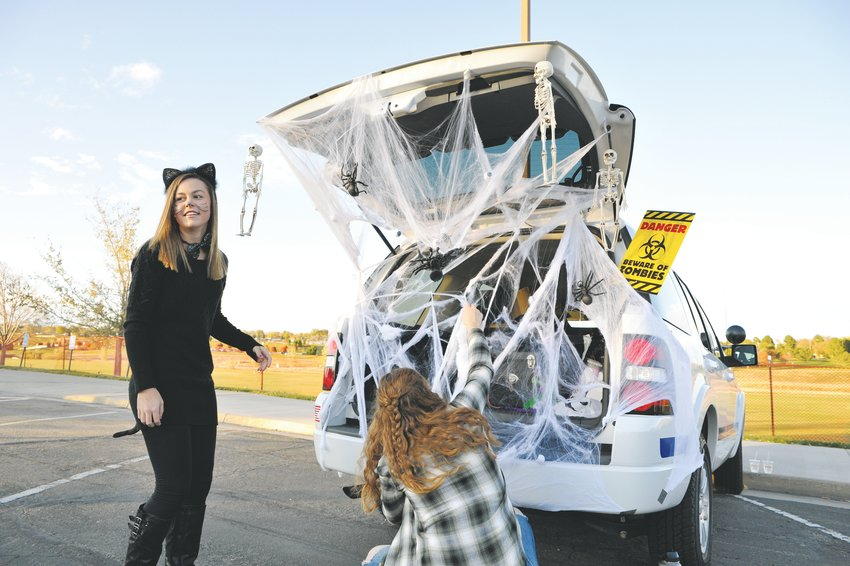 Abigail Brown, left, and Grace Redard, both Thornton Explorers, try and put the finishing touches on a Thornton Police Department cruiser, just before the official opening of the City's annual Trunk-or-Treat Halloween event Oct. 19, at Carpenter Park.