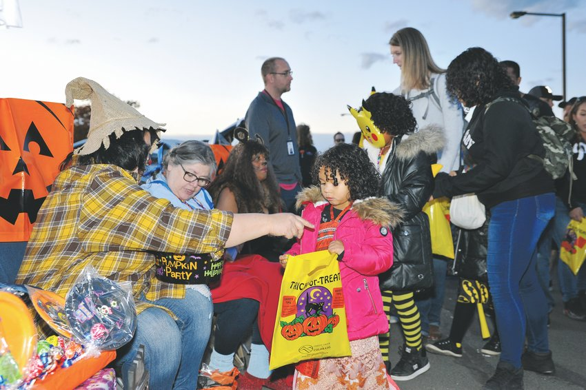 Chantel Brown, left, of Thornton, hands out candy during Thornton's 12th annual Trunk-or Treat, Saturday, Oct. 19, at Carpenter Park.