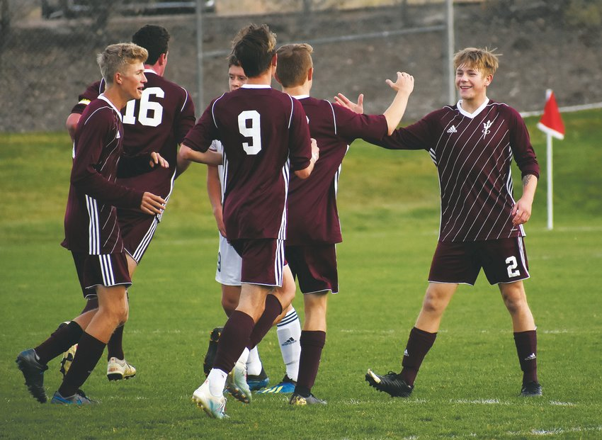 Golden senior Nate Thompson (2) is greeted by teammates after he scored in the 17th minute in the first half to tie Evergreen at 1-1. The Demons defeated the Cougars 3-1 on Oct. 17 at the North Area Athletic Complex to claim the Class 4A Jeffco League title for the second straight year.