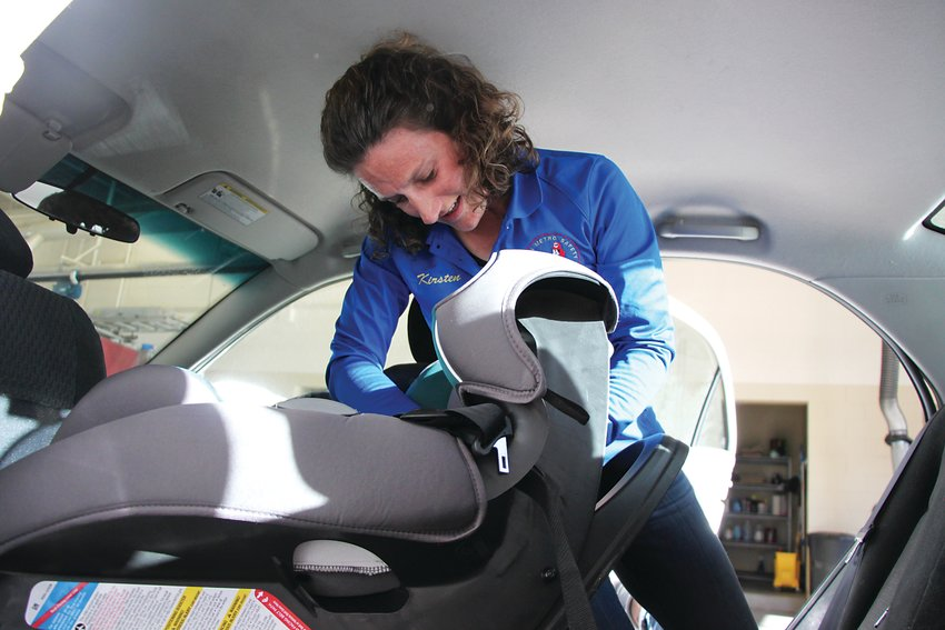 Kirsten Harbeck, a child passenger safety technician, wrestles with a child's car seat in the back of a Toyota at the Trailmark fire station on Oct. 22. Harbeck helps parents correctly install and use car seats for the South Metro Safety Foundation.