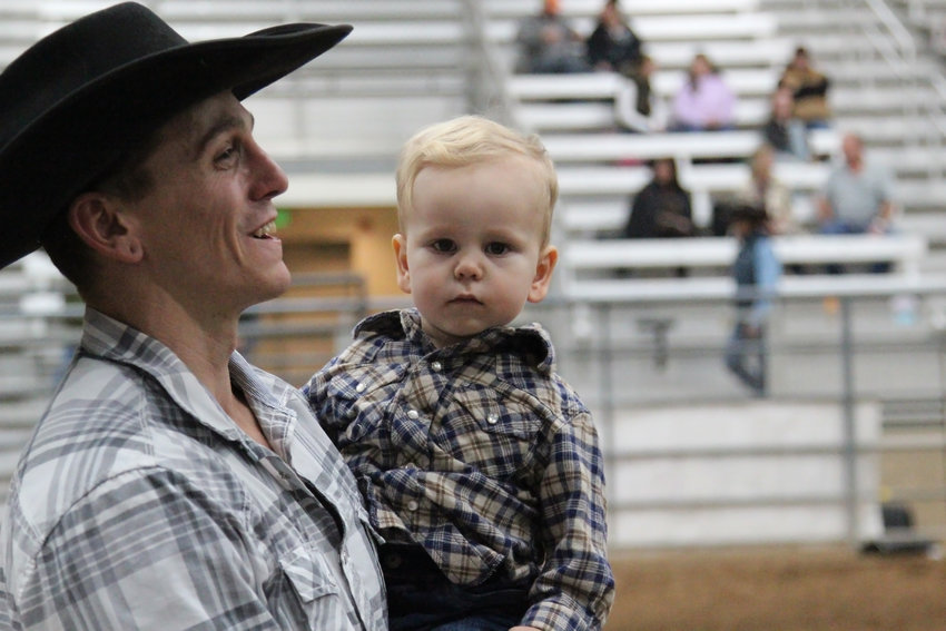 Michael Bryan holds his son, Kelton, 2, in the arena before the Buckers Unlimited finals began. Bryan retired from riding bulls after about 35 years in the sport.