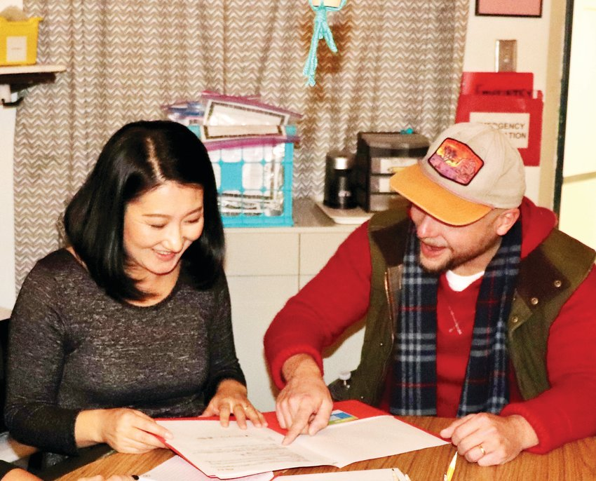 Second-grade parents Minako and Greg Hoflin review their child's academic data as part of Little Elementary's RISE night. The school provides both class data and individual student data so parents can better understand the needs of their children.
