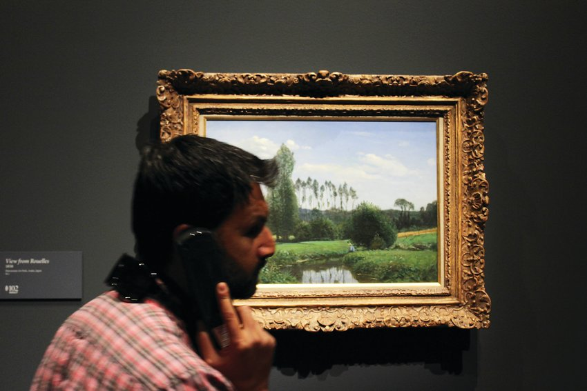 A man listens to the audio tour, stopping at the first known painting by Monet. The Monet exhibit features works from the artist's entire career.