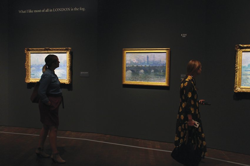 People walk by a series of Monet bridge paintings at the Denver Art Museum. Monet often painted the same subject at different times of day or in different lighting conditions in order to capture its essence.