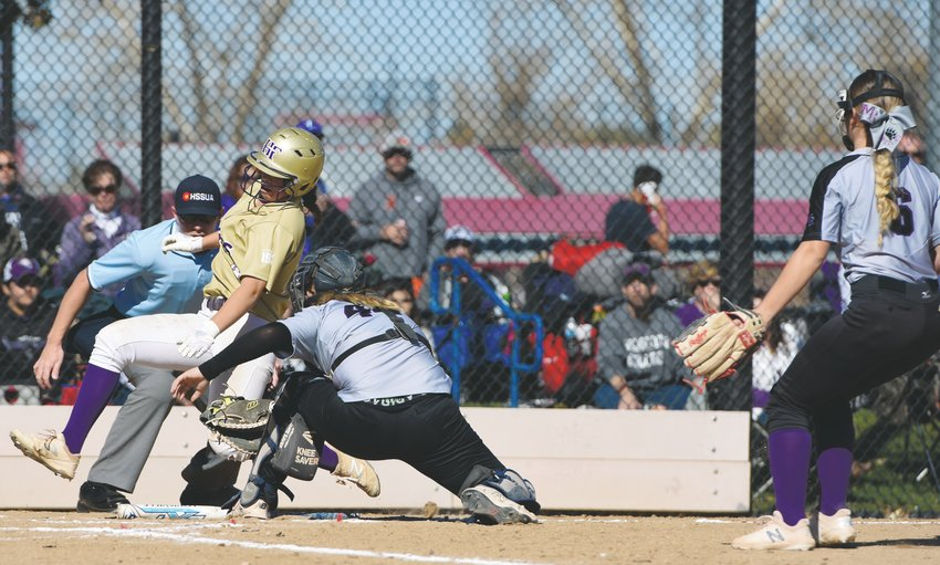 Holy Family's Ava Kuszak, left, eludes a tag at the plate by Mesa Ridge catcher Katrina Robertson, during the Tigers' first CHSAA 4A State Championship playoff game Oct. 25, at Aurora Sports Park. The Tigers shut out the Grizzlies, 19-0.