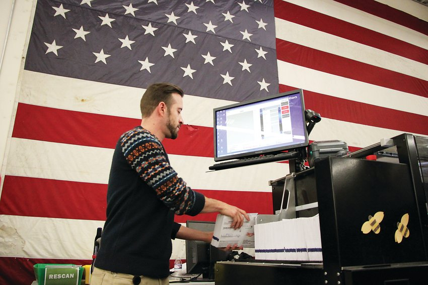 Ryan Ballard, an election mapping coordinator, feeds ballots into a ballot counting machine at Arapahoe County's election facility on Oct. 29. The machine can process up to 300 ballots a minute, though about half will be verified by hand.