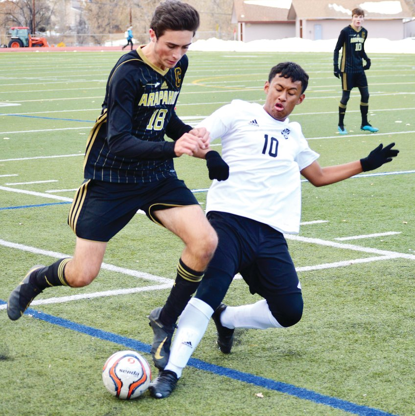 Arapahoe senior Garrett Lyles (18) attempts to get to the ball despite the efforts of Rangeview's Christian Valdez (10) during the first round boys soccer state playoff game on Nov. 1 at Littleton Public Schools Stadium. Arapahoe won 2-1 in overtime on a goal by Sam Myers.