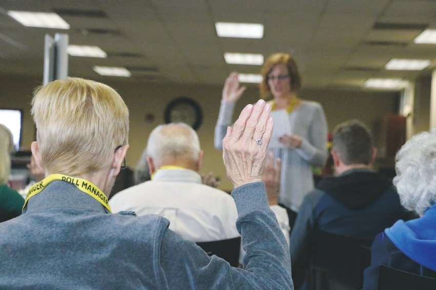 A paid volunteer is sworn in to work at the Douglas County Elections Headquarters Friday, Nov. 1. All workers must wear buttons indicating which party they are registered under.