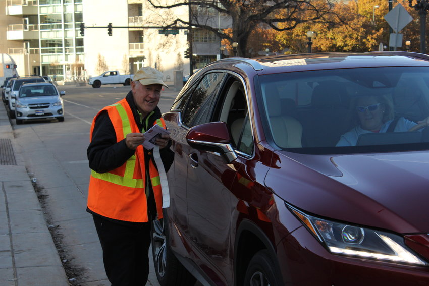 Mike Michalek takes a ballot from a voter at the drive-through drop  off site in front of the City and County Building on Election Day. He has worked at this site for the last four elections in Denver.