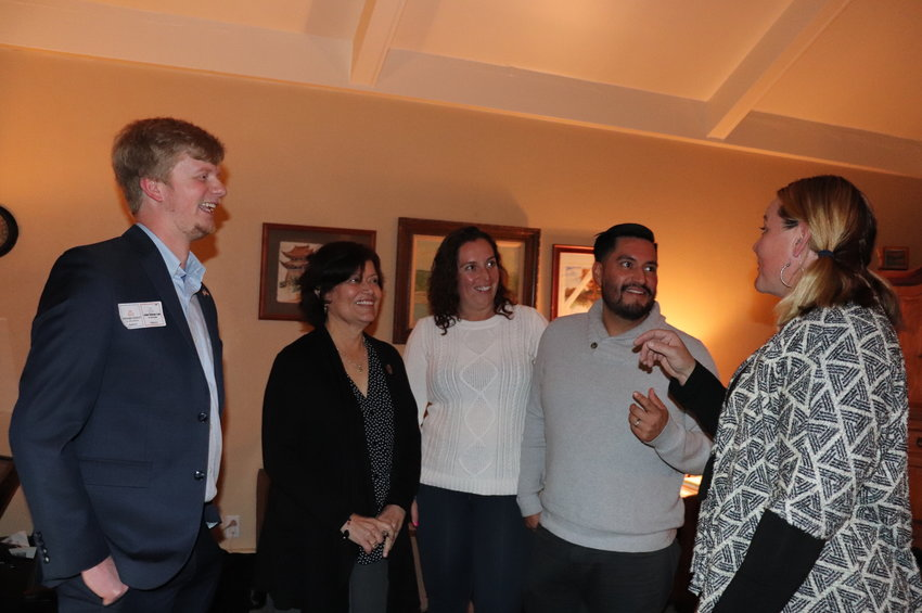 Candidates Stephanie Schooley, right, and Joan Chávez-Lee, second from left, who ran as a slate, mingle with friends during a watch party at Schooley's house.
