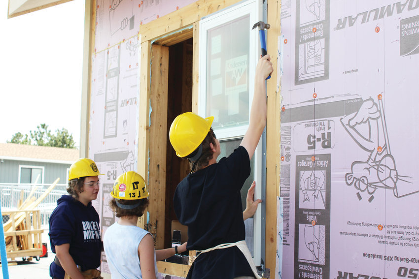 Students install windows for Green Mountain High School's house back in May.