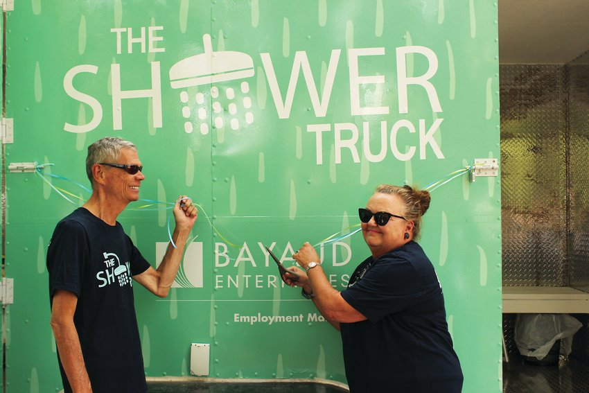 Dan Yagow, left, and Vikki Stevens cut the ribbon on the new shower truck. Stevens, who volunteers at various nonprofit organizations which provide resources for homeless people in Denver, donated $10,000 to Bayaud Enterprises to help build the truck.
