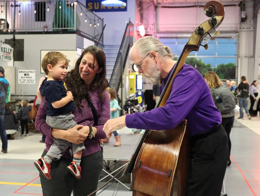 "Double Bass player Mike Fitzmaurice demonstrates how to play his instrument to a local family at Inside the Orchestra. ""It's my favorite gig, and I do a lot of different things,"" he said."